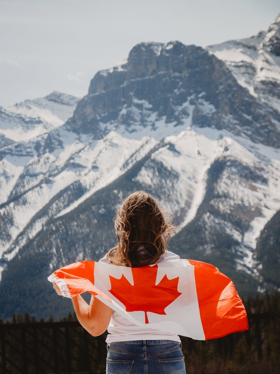 woman in orange and white shirt looking at snow covered mountains during daytime